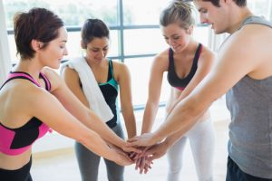 Four people in workout attire putting their hands together for a cheer