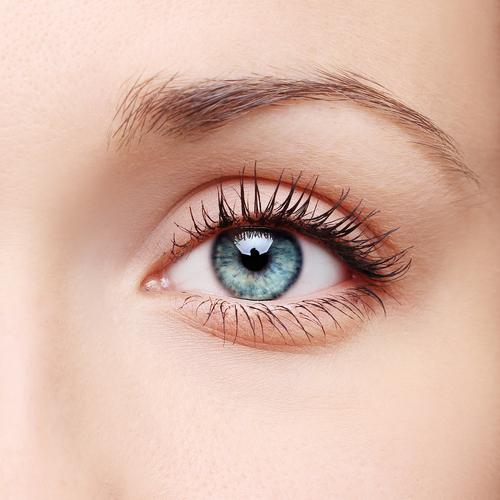Closeup of a human blue eye with beautiful, smooth skin
