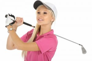 Young blonde woman in a pink shirt swinging a golf club